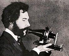 Alexander Graham Bell mluví do telefonu